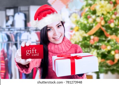 Picture of pretty girl showing a gift card and gift box while standing in the mall. Shot at Christmas time