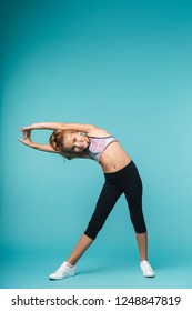 Picture of a pretty little girl child make fitness exercises isolated over blue wall.