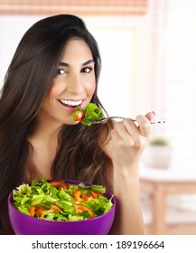 Picture of pretty woman eating green salad, closeup portrait of brunette female holding bowl with fresh vegetables on the kitchen, healthy lifestyle, organic nutrition, dieting concept