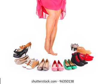 A picture of a pretty young woman sitting in the circle of shoes over white background