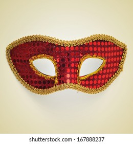 picture of a red and gold carnival mask on a beige background, with a retro effect