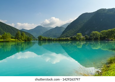 Picture of the river Soca. The clear, blue waters are perfectly calm, reflecting the scenery around. The hills around are covered in forest, and the sky is a bright blue with clouds on the far horizon