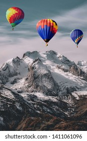 Picture of a rocky snowy mountain with three air balloons