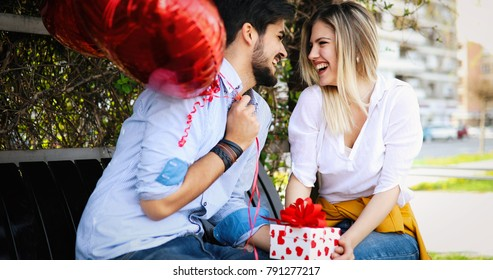 Picture of romantic couple standing outside with baloons