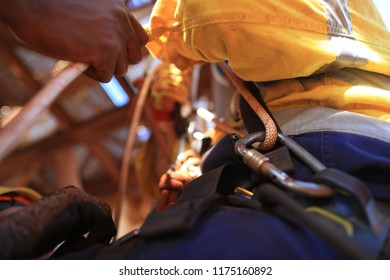Picture of rope access locking carabiner with white rope clipping into secondary safety back up point on side harness, abseiler abseiling down with casualty during team rescue rehearsal Australia