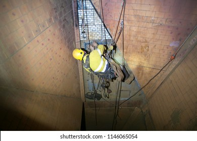 Picture of rope access miner abseiling down hanging in fall arrest position commencing using solid square tool  measurement metal wall at construction site Perth, Australia