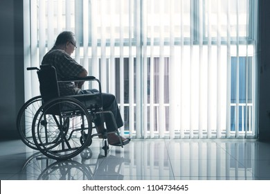 Picture of sad elderly man sitting in the wheelchair while looking out the window in the retirement home