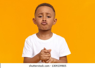 Picture for sad frustrated ten year old dark skinned child wearing white t-shirt pouting lips, having mournful facial expression, feeling sorry for misbehavior, asking parents not to punish him