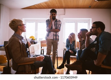 Picture of a sad shaken terrified young man in a group therapy talking about his experience.