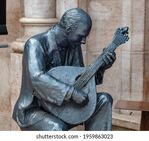A picture of a sculpture showing a Portuguese guitar player, representing the Fado music genre, traditional of Portugal (Lisbon).