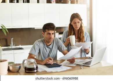 Picture of serious young American couple spending weekend morning in kitchen, doing paperwork, looking through mail and calculating family expenses, paying bills online using laptop computer
