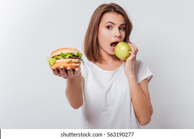 Picture of serious young woman standing over white background while holding fastfood and eating apple
