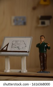 picture of a set of toys on architecture with an architect, his table, on the wall his tools and house