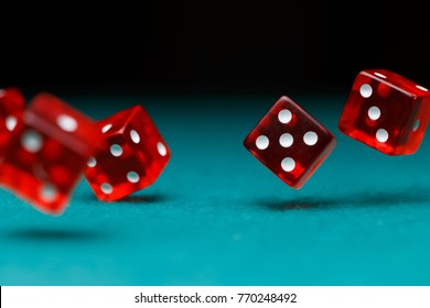 Picture of several red dice falling on green table