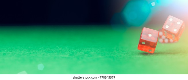Picture of several red dice falling on green table at background of multicolored spots