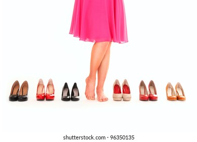 A picture of sexy female legs among six pairs of shoes over white background