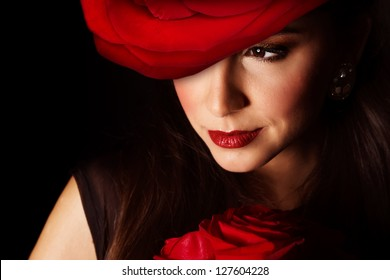Picture of sexy woman with big red rose hat on the head isolated on black background, closeup portrait of stylish girl with flowers bouquet, Valentine day, beauty and styling salon, elegance concept