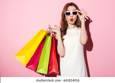 Picture of a shocked young brunette woman in white summer dress wearing sunglasses posing with shopping bags and looking at camera over pink background.