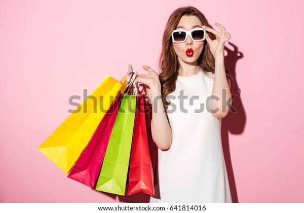 Foto van een geschokte jonge brunette vrouw in witte zomerjurk dragen zonnebril poseren met boodschappentassen en kijken naar camera over roze achtergrond.