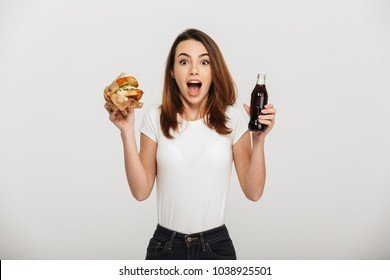 Picture of shocked young woman standing isolated over grey wall background eating a burger drinking soda.