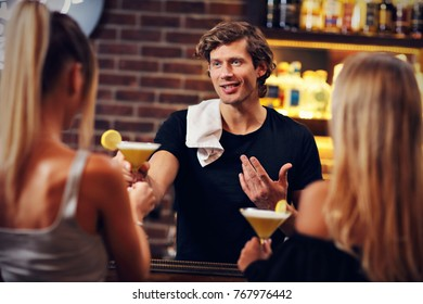 Picture showing handsome bartender serving cocktails in a pub