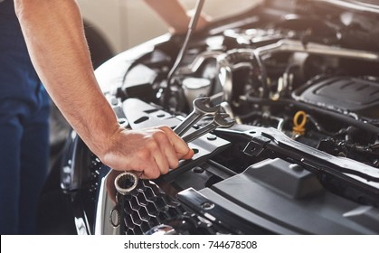 Picture showing muscular car service worker repairing vehicle.
