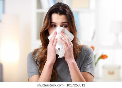 Picture showing woman sneezing on tissue on couch in the living-room