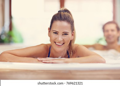 Picture showing young couple enjoying jacuzzi in hotel spa