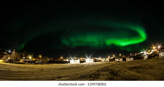 Picture shows a camping van under northern lights in Norway