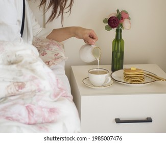 The picture shows a female hand pouring milk into her coffee  There is a stack of pancakes on the nightstand