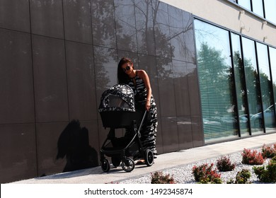 The picture shows a mother standing together with a pram, looking after a child against the backdrop of a modern building.
