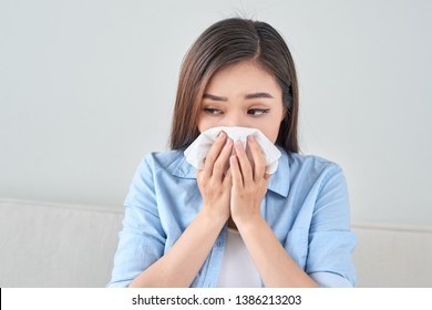 Picture of a sick young lady sitting on the couch and blowing her runny nose
