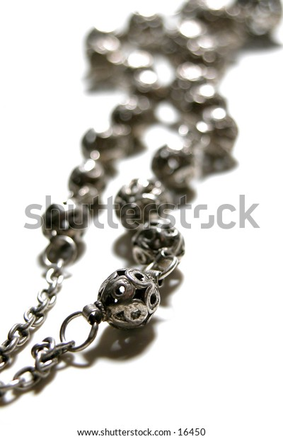 A picture of a silver necklace with rosaries.
