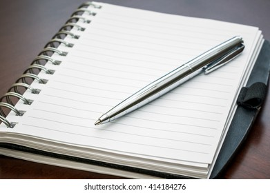 Picture of a silver pen and folded spiral notebook lying on a dark brown wooden desk