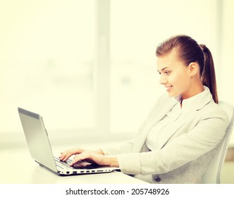 picture of smiling businesswoman with laptop in office
