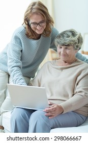 Picture of smiling carer teaching old woman computer skills