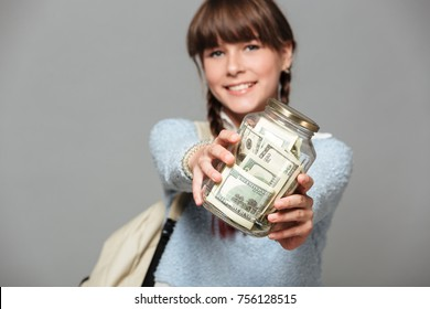 Picture of smiling girl standing isolated grey background with jar full of money. Looking camera holding backpack.