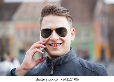Picture of smiling guy with sunglasses talking on the phone in the city downtown