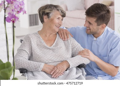 Picture of a smiling senior woman and her male caregiver, light interior
