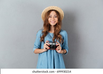 Picture of smiling young caucasian woman photographer holding camera.