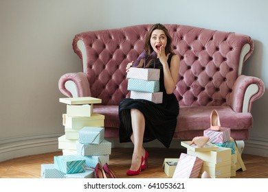 Picture of smiling young lady sitting on sofa indoors choosing shoes. Looking at camera.
