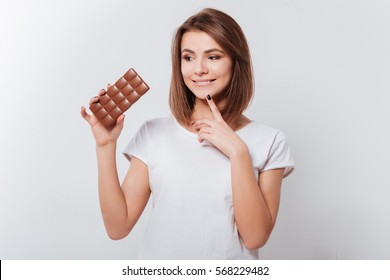Picture of smiling young lady standing over white background while holding chocolate