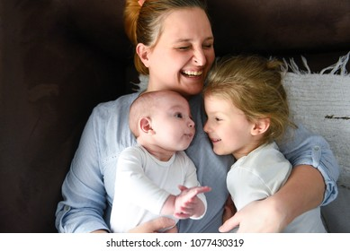 Picture of smiling young mother hugging two little children, closeup portrait of happy family, cute brunette female with daughter and son indoor