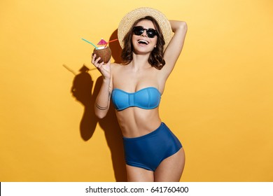 Picture of smiling young woman in swimwear isolated over yellow background holding cocktail.
