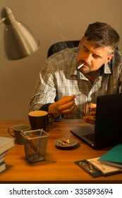 Picture of smoking bearded man at untidy desk