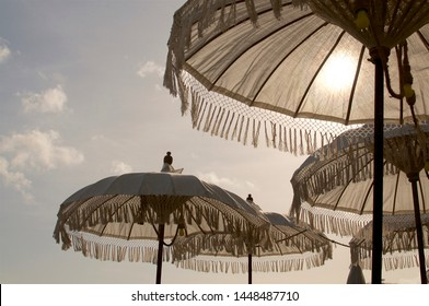 Picture of some beautiful white Balinese sun umbrella during sunset, decorated with yellow bulb lights and located at the famous Echo Beach in Canggu, Bali - Indonesia