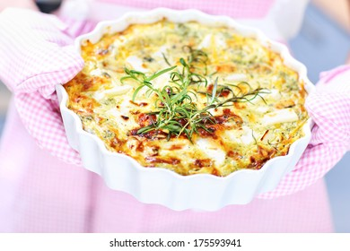 A picture of a spinach quiche hold in oven gloves over pink apron