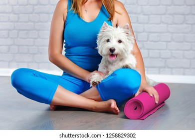 Picture of a sportivewoman holding yoga mat and a dog
