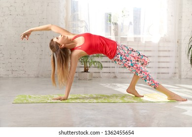 Picture of sporty beautiful blond young woman in sportswear working out in hall, doing Variation of Bridge Pose. Young sporty female practicing yoga.