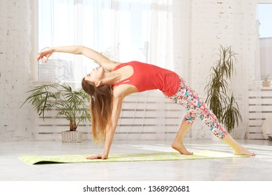 Picture of sporty beautiful blond young woman in sportswear working out in hall, doing Variation of Bridge Pose. Young sporty female practicing yoga. -